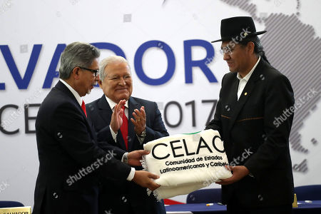 Foreign Minister of El Salvador, Carlos Castaneda (L), delivers along with Salvadoran president, Salvador Sanchez Ceren (C), the flag that symbolizes the protempore Presidency of CELAC, to Bolivian Foreign Minister, Diego Pary Rodríguez, in San Salvador, El Salvador, 14 January 2019. Bolivia received today in the Salvadoran capital the Protempore Presidency of the Community of Latin American and Caribbean States (Celac), an intergovernmental mechanism of dialogue and political agreement that will be led by the South American country until 2020.