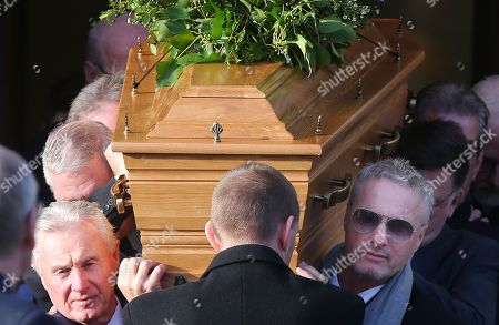 Eddie Irvine (right) helps carry the coffin from the church after the service.