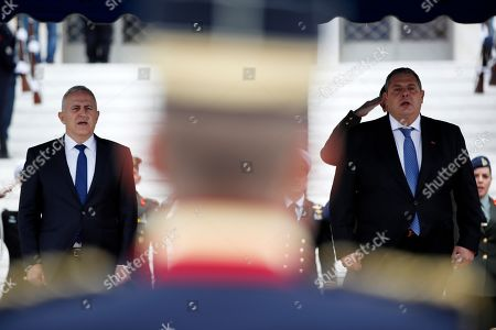 Newly appointed Defense Minister Evangelos Apostolakis, left, and outgoing Panos Kammenos, sing the national anthem during the handover ceremony in Athens, . The 62-year-old retired admiral left his post as head of the country's armed forces to replace Panos Kammenos, leader of a small nationalist party, who withdrew from the government coalition at the weekend over disagreement on a proposed deal between Greece and neighbor Macedonia. Greece's parliament has scheduled a confidence vote for late Wednesday following the collapse of Prime Minister Alexis Tsipras' governing coalition over a proposed deal to end a decades-old dispute with Macedonia
