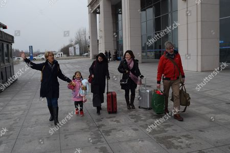 Alice Simpson sets off from Nanzhang station on the first leg of her journey to England with grandparents Ian and Linda and their lawyers
