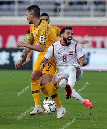 Syria's midfielder Mahmoud al Maowas, right, duels for the ball with Australia's forward Jamie Maclaren during the AFC Asian Cup group B soccer match between Australia and Syria at the Khalifa bin Zayed Stadium in Al Ain, United Arab Emirates