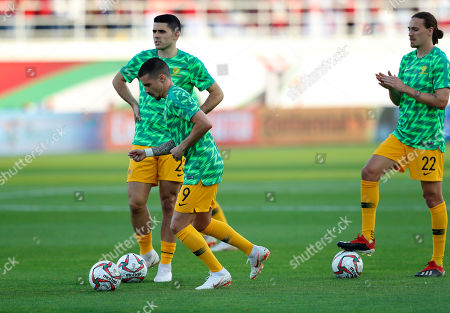 Australian players Australia's forward Jamie Maclaren, center, Tomas Rogic, left, and Australia's midfielder Jackson Irvine, right, warm up before the starting game of the AFC Asian Cup group B soccer match between Australia and Syria at the Khalifa bin Zayed Stadium in Al Ain, United Arab Emirates