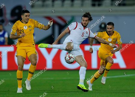 Syria's defender Omro Midani, center, kicks the ball between two Australian players Jamie Maclaren, right, and Tomas Rogic, left, during the AFC Asian Cup group B soccer match between Australia and Syria at the Khalifa bin Zayed Stadium in Al Ain, United Arab Emirates