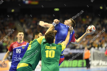 Gleb Kalarash of Russia (R) in action against Thiago Ponciano of Brazil (2-L) and Jose Toledo of Brazil (3-L) during the match between Russia and Brazil at the IHF Men's Handball World Championship in Berlin, Germany, 15 January 2019.