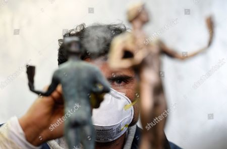 Foundry worker Ricardo Gortinez applies a blue-green patina to Actor statuettes during the 25th Annual Casting of the Screen Actors Guild Awards at American Fine Arts Foundry, in Burbank, Calif. The SAG Awards will held on Sunday, Jan. 27 in Los Angeles