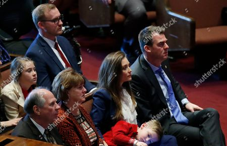Oklahoma Governer Kevin Stitt, right, sits with his wife, Sarah Stitt, second from right, son Houston Stitt, center, and his parents, John and Joyce Stitt, left, during the inaugural prayer servce in Moore, Okla