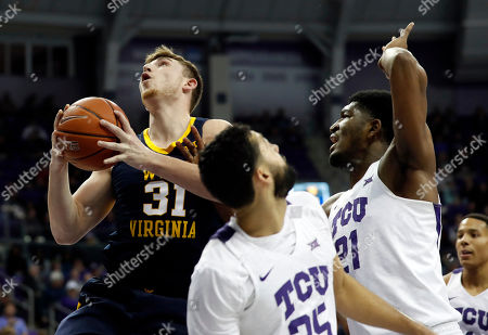 West Virginia forward Logan Routt (31) leaps to the basket for a shot as TCU guard Alex Robinson (25) and center Kevin Samuel (21) defend in the first half of an NCAA college basketball game, in Fort Worth, Texas