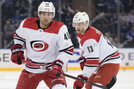 Victor Rask, Warren Foegele. Carolina Hurricanes center Victor Rask (49) and left wing Warren Foegele (13) watch a loose puck during the first period of an NHL hockey game against the New York Rangers, at Madison Square Garden in New York
