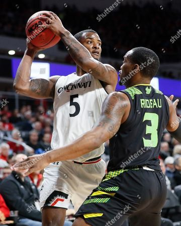 Trevor Moore, LaQuincy Rideau. Cincinnati's Trevor Moore (5) passes against South Florida's LaQuincy Rideau (3) in the first half of the team's NCAA college basketball game, in Cincinnati