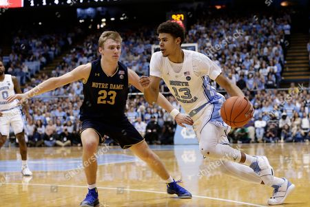 North Carolina's Cameron Johnson (13) dribbles while Notre Dame's Dane Goodwin (23) defends during the first half of an NCAA college basketball game in Chapel Hill, N.C