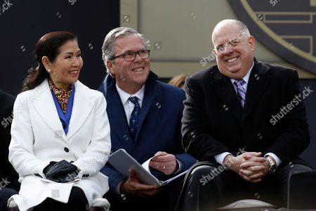 Larry Hogan, Jeb Bush, Yumi Hogan. Maryland Gov. Larry Hogan, right, laughs alongside first lady Yumi Hogan, left, and former Florida Gov. Jeb Bush during Hogan's inauguration ceremony, in Annapolis, Md. Hogan is the first Republican governor to be re-elected in the state since the 1950s