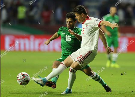 Iraq's defender Ahmad Ibrahim, foreground, fights for the ball with Iran's midfielder Mehdi Torabi, background, during the AFC Asian Cup group D soccer match between Iran and Iraq at the Al Maktoum Stadium in Dubai, United Arab Emirates