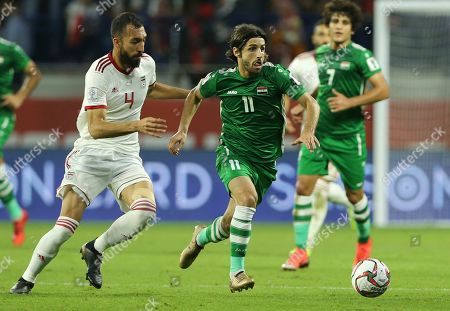 Iraq's Midfielder Humam Tariq, right, runs for the ball with Iran's defender Rouzbeh Cheshmi, left, during the AFC Asian Cup group D soccer match between Iran and Iraq at the Al Maktoum Stadium in Dubai, United Arab Emirates