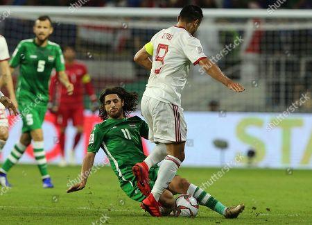 Iraq's Midfielder Humam Tariq, center, tackled Iran's midfielder Omid Ebrahimi, foreground, during the AFC Asian Cup group D soccer match between Iran and Iraq at the Al Maktoum Stadium in Dubai, United Arab Emirates