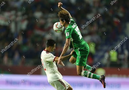 Iraq's forward Mohanad Ali, right, jumps for the ball against Iran's midfielder Omid Ebrahimi, left, during the AFC Asian Cup group D soccer match between Iran and Iraq at the Al Maktoum Stadium in Dubai, United Arab Emirates