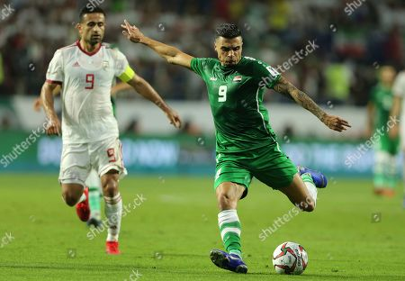 Iraq's Midfielder Ahmed yasin, right, kicks the ball against Iran's midfielder Omid Ebrahimi, left, during the AFC Asian Cup group D soccer match between Iran and Iraq at the Al Maktoum Stadium in Dubai, United Arab Emirates