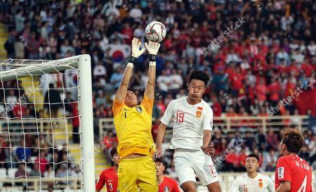 Kim Seung-gyu of South Korea boxing the ball in front of Liu Yang of China during South Korea v China at the Al-Nahyan Stadium in Abu Dhabi, United Arab Emirates, AFC Asian Cup, Asian Football championship