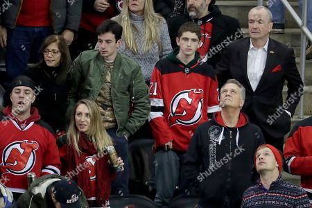 Stock Image of New Jersey Gov. Phil Murphy, top right, looks on while standing with his wife, Tammy Murphy, top left, and their sons Josh Murphy, top center left, and Charlie Murphy, top center right,during the third period of an NHL hockey game between the New Jersey Devils and the Chicago Blackhawks, in Newark, N.J. The Devils won 8-5