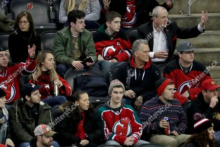 New Jersey Gov. Phil Murphy, top right, reacts while sitting with his wife, Tammy Murphy, top left, and their sons Josh Murphy, top center left, and Charlie Murphy, top center right,during the third period of an NHL hockey game between the New Jersey Devils and the Chicago Blackhawks, in Newark, N.J. The Devils won 8-5