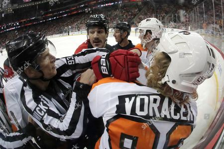 NHL linesman Brian Murphy, left, tries to breakup a scuffle between Philadelphia Flyers right wing Jakub Voracek (93), of the Czech Republic, and New Jersey Devils center Brian Boyle (11) during the second period of an NHL hockey game, in Newark, N.J