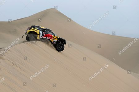 Driver Sebastien Loeb, of France, and co-driver Daniel Elena, of Monaco, race their Peugeot during the stage nine of the Dakar Rally in Pisco, Peru