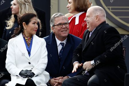 Maryland Gov. Larry Hogan, right, chats with first lady Yumi Hogan and former Florida Gov. Jeb Bush at his inauguration ceremony, in Annapolis, Md