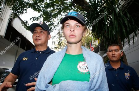 Thai Immigration police officers escort Belarusian model Anastasia Vashukevich, center, from the Immigration Detention Center towards a vehicle to take her to an airport for deportation, in Bangkok, Thailand, . Thai police says it will deport Vashukevich who claimed that she had evidence of Russian involvement in helping elect Donald Trump as U.S. president after she pleaded guilty in a case related to holding a sex training seminar in Thailand