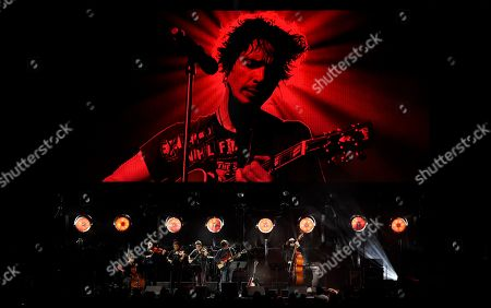 """Ryan Adams performs with his band underneath an image of the late singer Chris Cornell during """"I Am The Highway: A Tribute to Chris Cornell"""" at The Forum, in Inglewood, Calif"""