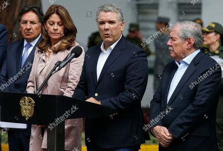 Colombia's President Ivan Duque gives a statement inside the General Santander police academy after a bomb exploded on the campus in Bogota, Colombia, . At right is Defense Minister Guillermo Botero and at left is Vice President Martha Lucia Ramirez