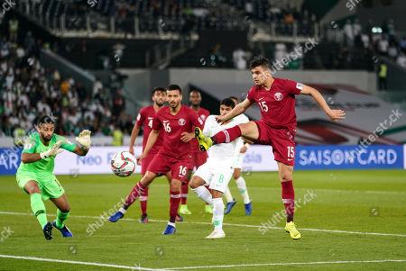 Bassam Al-Rawi of Qatar kicking the ball away in front of Yahya Al-Shehri of Saudi Arabia during Saudi Arabia v Qatar at the Zayed Sports City Stadium in Abu Dhabi, United Arab Emirates, AFC Asian Cup, Asian Football championship