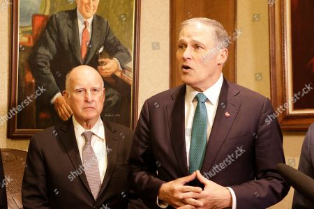 Washington Gov. Jay Inslee, left, speaks to the media as former California Gov. Jerry Brown looks, in Olympia, Wash., . Inslee, Brown and several Washington lawmakers met to discuss Inslee's climate agenda