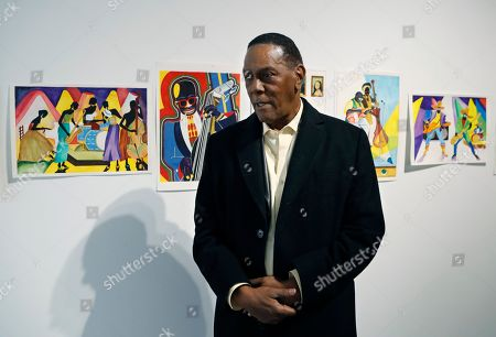 Richard Phillips stands next to some of his artwork during an interview at the Community Art Gallery in Ferndale, Mich. Phillips was exonerated of murder in 2018 after 45 years in prison. Lawyers say he should be entitled to more than $2 million under Michigan's wrongful conviction law, but the state so far is resisting. So Phillips, 73, is selling some of his 400-plus watercolors that he painted in prison