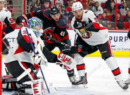 Carolina Hurricanes' Jordan Martinook (48) works between Ottawa Senators goaltender Anders Nilsson (31) and Senators' Cody Ceci (5) during the first period of an NHL hockey game, in Raleigh, N.C