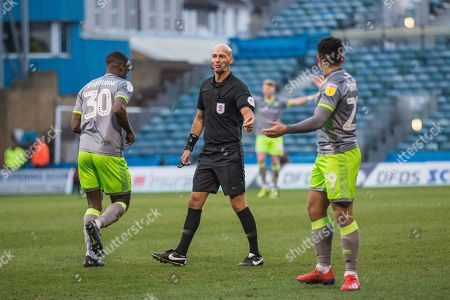 Referee Darren Dysdale looks at Isaiah Osbourne (Walsall) as Josh Gordon (Walsall) continues his protest during the EFL Sky Bet League 1 match between Gillingham and Walsall at the MEMS Priestfield Stadium, Gillingham