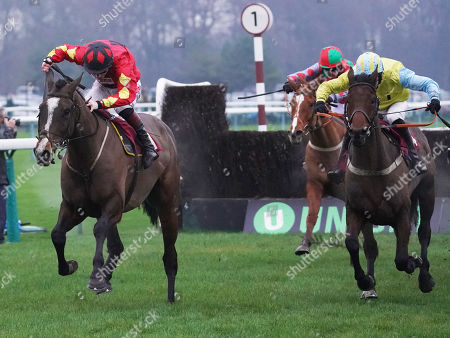 Haydock Park Racecourse. The Peter Marsh Handicap Steeple Chase. Wakanda ridden by Danny Cook (yellow) clears the final fence to win from Ballyarthur ridden by James Bowen.