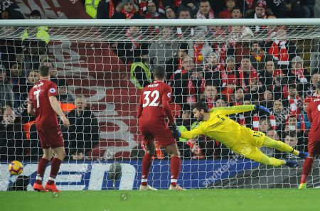 Liverpool's Alisson Becker dives but fails to stop a shot by Crystal Palace's James Tomkins during the English Premier League soccer match between Liverpool and Crystal Palace at Anfield in Liverpool, England