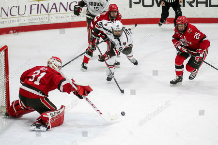 Stock Picture of NFL: Minnesota Vikings at New England Patriots. St. Lawrence's Arthur Brey (31) and Michael Laidley (25) and Brown's Colin Burston (28) go after a loose puck during an NCAA hockey game on in Providence, R.I