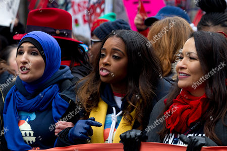 Co-presidents of the 2019 Women's March, Linda Sarsour, left, and Tamika Mallory, center, join other demonstrators on Pennsylvania Avenue during the Women's March in Washington on