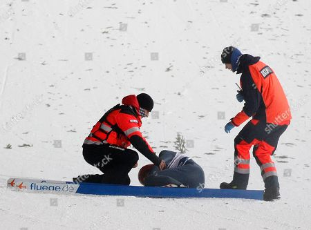 Rescue medics help Germany's David Siegel after he fell, during his final jump of the 17th World Cup Ski Jumping competition in Zakopane, Poland
