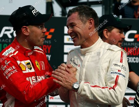 Team Nordic driver Tom Kristensen, of Denmark, right, celebrates his team's victory with second-place Team Germany finisher Sebastian Vettel following the Race of Champions Nations Cup in Foro Sol in Mexico City, . The Race of Champions is being held for the first time in Latin America