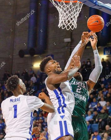 Buffalo Bulls forward Montell McRae (1) looks on as forward Nick Perkins (33) battles for a rebound with Eastern Michigan Eagles center James Thompson IV (2) during the second half of play in the NCAA Basketball game between the Eastern Michigan Eagles and Buffalo Bulls at Alumni Arena in Amherst, N.Y. (Nicholas T. LoVerde/UB Athletics)