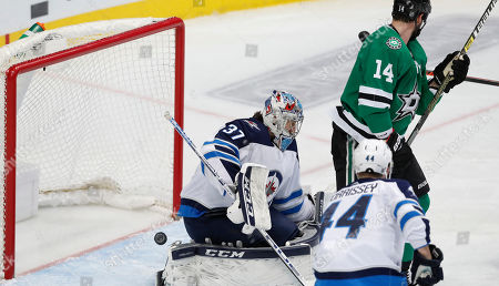 Winnipeg Jets goaltender Connor Hellebuyck (37) gives up a goal to Dallas Stars right wing Brett Ritchie, not seen, as Stars left wing Jamie Benn (14) and Jets defenseman Josh Morrissey (44) watch during the first period of an NHL hockey game in Dallas