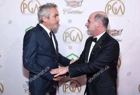 Alfonso Cuaron, Matthew Weiner. Alfonso Cuaron, left, and Matthew Weiner speak as they arrive at the Producers Guild Awards, at the Beverly Hilton Hotel in Beverly Hills, Calif