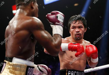 Manny Pacquiao, right, fights Adrien Broner in a welterweight championship boxing match, in Las Vegas