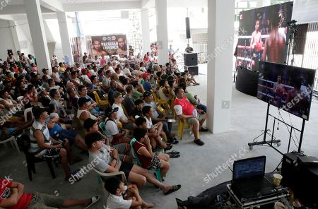 Filipino spectators watch a live broadcast from Las Vegas, USA of the boxing match between Filipino boxer Manny 'Pacman' Pacquiao and American boxer Adrien Broner for the World Boxing Association world welterweight championship title, at a village hall in Marikina city, east of Manila, Philippines, 20 January2019. Pacquiao won by unanimous decision.