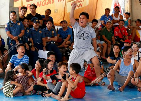 Fans cheer during the WBA Welterweight Championship boxing match between Filipino Manny Pacquiao and American Adrien Broner, in Manila, Philippines, which was beamed live via satellite from Las Vegas. Pacquiao retained the title via unanimous decision