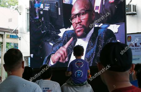 Fans watch the reaction of Floyd Mayweather Jr. following the WBA Welterweight Championship fight between Filipino Manny Pacquiao and American Adrien Broner, in Manila, Philippines, and beamed live via satellite from Las Vegas. Pacquiao retained the title via unanimous decision