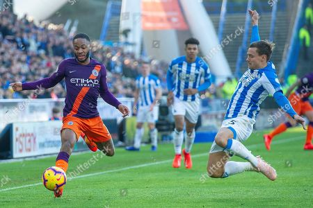 Raheem Sterling of Manchester City is tackled by Chris Lowe of Huddersfield Town during the Premier League match between Huddersfield Town and Manchester City at the John Smiths Stadium, Huddersfield