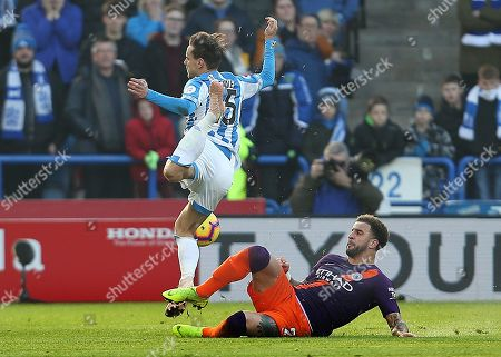 Kyle Walker of Manchester City is shown a yellow card for this challenge on Chris Lowe of Huddersfield Town