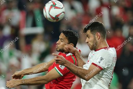 Oman's forward Mohammed Al Ghassani, left, heads the ball past Iran's defender Morteza Pouraliganji during the AFC Asian Cup round of 16 soccer match between Iran and Oman at Mohammed Bin Zayed Stadium in Abu Dhabi, United Arab Emirates